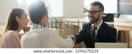 Confident real estate agent financial advisor in suit shaking hands with client respect gratitude gesture, congratulate with property purchase tenancy renting concept, banner for website header design #1296270229