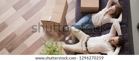 Horizontal above concept photo married couple at moving day rest relax on couch cardboard boxes on floor feels satisfied breathing fresh air, banner for website header design with copy space for text