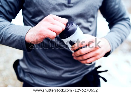 Midsection of athlete opening water bottle in outdoor training #1296270652