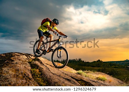 Cyclist Riding the Mountain Bike on the Rocky Trail at Sunset. Extreme Sport and Enduro Biking Concept. #1296324679