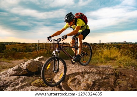 Cyclist Riding the Mountain Bike on the Rocky Trail at Sunset. Extreme Sport and Enduro Biking Concept. #1296324685