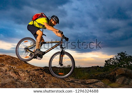 Cyclist Riding the Mountain Bike on the Rocky Trail at Sunset. Extreme Sport and Enduro Biking Concept. #1296324688