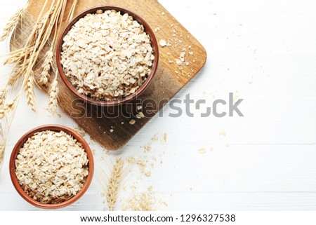 Oatmeal in bowls on white wooden table #1296327538
