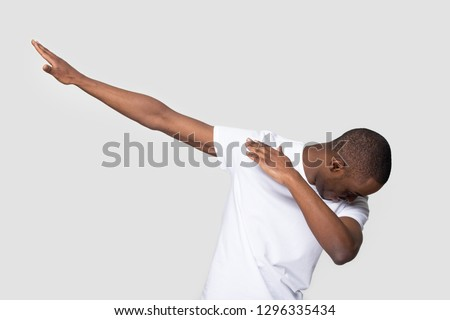 Happy black man making dab arms gesture on blank white grey studio background, funny african guy dabbing moving in internet meme pose celebrating victory having fun, dance school or triumph concept