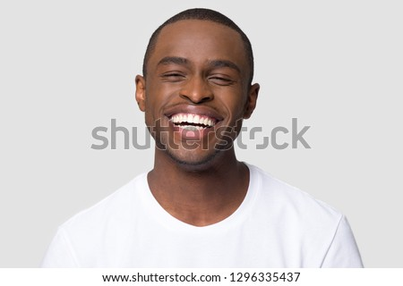 Cheerful happy african millennial man laughing looking at camera isolated on studio blank background, funny young black guy with healthy teeth beaming orthodontic white wide smile head shot portrait #1296335437