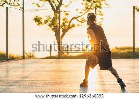 black man doing sports, playing basketball on sunrise, active lifestyle, sunny summer morning #1296360595
