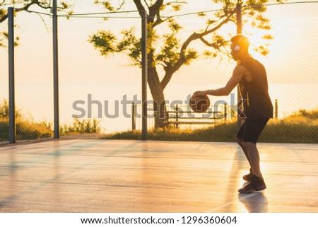 black man doing sports, playing basketball on sunrise, active lifestyle, sunny summer morning #1296360604