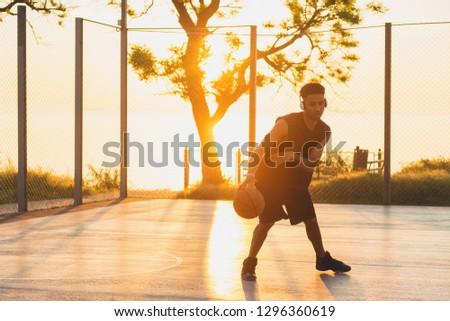 black man doing sports, playing basketball on sunrise, active lifestyle, sunny summer morning #1296360619