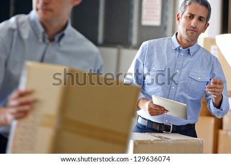 Manager Using Tablet Computer In Distribution Warehouse #129636074