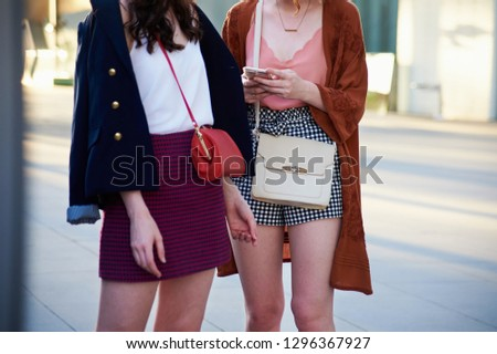 Street style image of two young women wearing mini skirts, casual tops and cross body bags, mid section, horizontal #1296367927