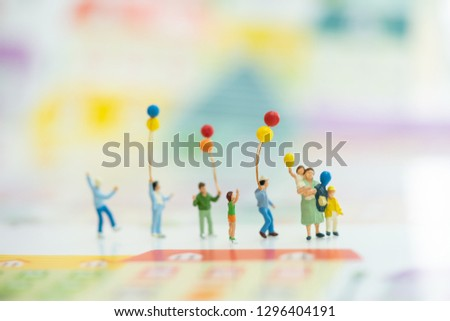 Miniature people, family and children with colorful balloons  standing. International Day of Families #1296404191
