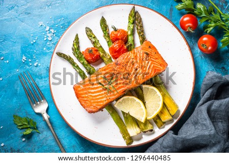 Grilled salmon fish fillet with asparagus and tomato. Top view on blue stone table. #1296440485