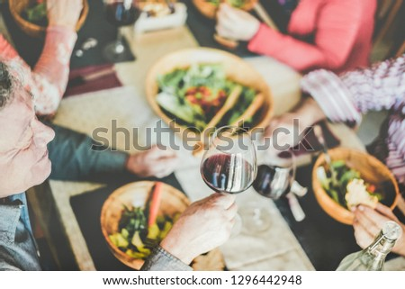 Happy mature people eating at restaurant sunday lunch - Senior friends having fun eating and drinking red wine - Joyful elderly lifestyle, food and friendship concept - Focus on left man nose #1296442948