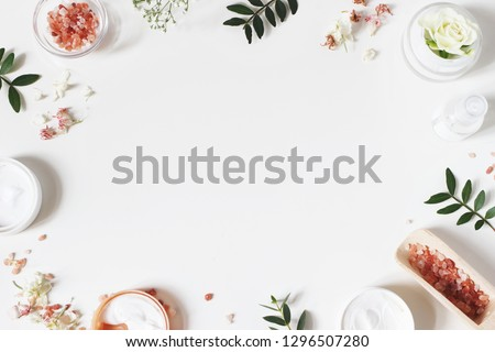 Styled beauty frame, web banner. Skin cream, tonicum bottle, dry flowers, leaves, rose and Himalayan salt. White table background. Organic cosmetics, spa concept. Empty space, flat lay, top view. #1296507280