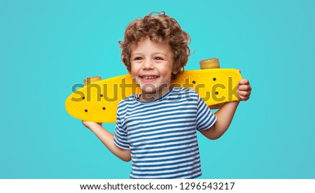 Charming curly boy holding yellow pennyboard and looking away isolated on aqua blue background. Royalty-Free Stock Photo #1296543217