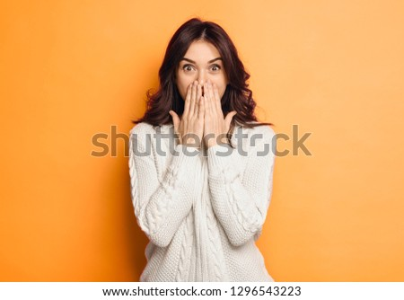 Portrait of amazed young woman over orange background #1296543223