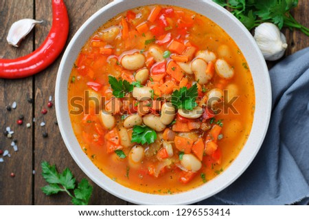 Vegetable Soup with White Beans, Homemade Soup on Dark Wooden Background, Vegetarian Food, Top View #1296553414