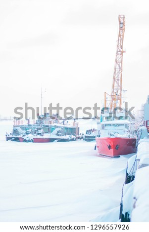 The ship and other water vessels are frozen in the port. Winter cold day at the river port. Red small ship near the pier covered with ice. Gray sky and frozen river. Everything is covered with snow. #1296557926