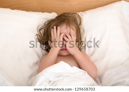 Toddler Girl closing her eyes in the bed, perhaps she is seeing bad dreams. #129658703