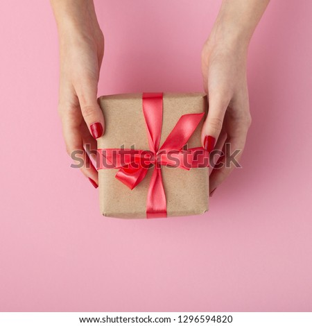 girl holding a present in hands, women with gift box in hands wrapped in decorative paper on a pastel colored pink background, top view, concept holiday and gifts #1296594820