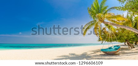 Tropical beach panorama as summer landscape with beach swing or hammock and white sand and calm sea for beach banner. Perfect beach scene vacation and summer holiday concept. Boost up color process  #1296606109