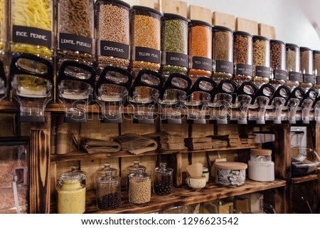 Shelf with raw food products displayed in refillable food dispensers. Food shop interior in package free grocery store. Royalty-Free Stock Photo #1296623542