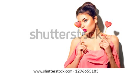 Beauty joyful Young fashion model Girl with Valentine Heart shaped cookies in her hands. Love Concept. Beautiful smiling young woman. Kiss. Valentines Day gift. Isolated on white background #1296655183
