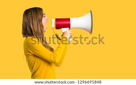 young girl with yellow sweater shouting through a megaphone to announce something in lateral position on isolated yellow background #1296695848