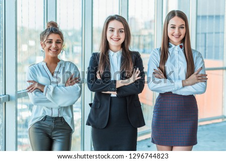 With pleasure, three business women cross their arms, looking at the camera. #1296744823