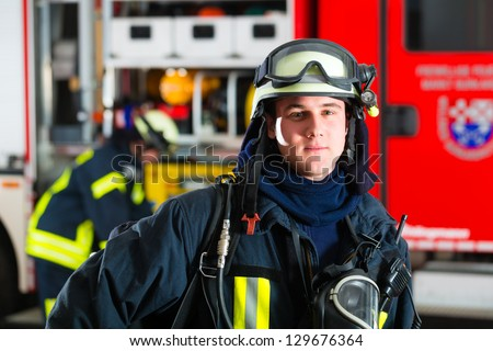 young fireman in uniform standing in front of firetruck, he is ready for deployment #129676364
