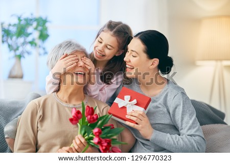 Happy women's day! Child daughter is congratulating mom and granny giving them flowers tulips. Grandma, mum and girl smiling and hugging. Family holiday and togetherness. #1296770323