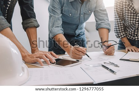Engineers discuss a blueprint while checking information on a tablet computer in a office. Royalty-Free Stock Photo #1296777055
