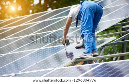 Construction worker connecting photo voltaic panel to solar system using screwdriver on shiny surface and lit by sun green tree background. Alternative energy and financial investment concept. #1296804976