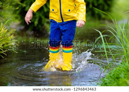 Kid playing in the rain in autumn park. Child jumping in muddy puddle on rainy fall day. Little boy in rain boots and yellow jacket outdoors in heavy shower. Kids waterproof footwear and coat. #1296843463