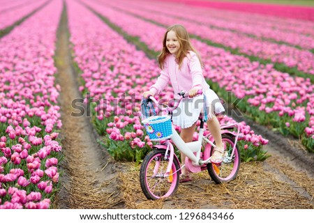 Child riding bike in tulip flower field during family spring vacation in Holland. Kid cycling in pink tulips. Little girl cycling in the Netherlands. European trip with kids. Travel with children. #1296843466