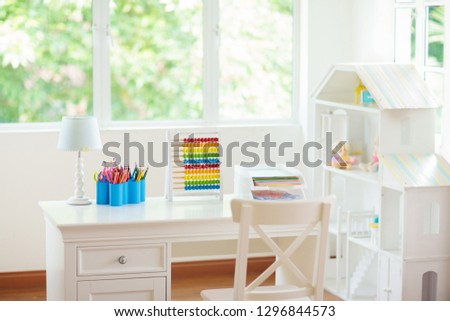 Kids bedroom with wooden desk and doll house. White sunny room with big window for young child. Home interior for little girl. Table for homework and study with lamp and abacus, books for school kid. #1296844573