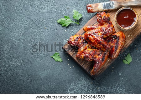Roasted chicken wings in barbecue sauce with sesame seeds and parsley on a wooden board on a concrete table. Top view with copy space. Tasty snack for beer on a dark background. Flat lay. #1296846589