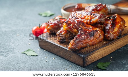 Roasted chicken wings in barbecue sauce with sesame seeds and parsley on a wooden board on a concrete table. With copy space. Tasty snack for beer on a dark background. #1296846613