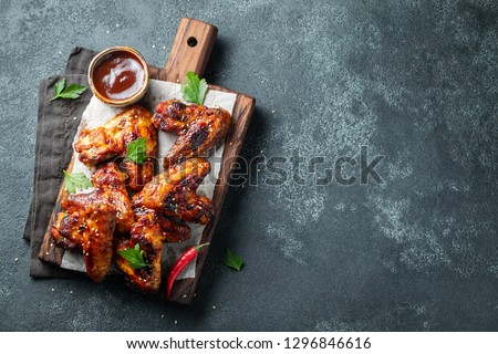 Roasted chicken wings in barbecue sauce with sesame seeds and parsley on a wooden board on a concrete table. Top view with copy space. Tasty snack for beer on a dark background. Flat lay. #1296846616