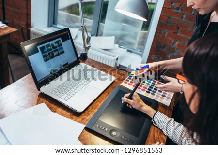 Team of female interior designer drawing a new project using graphic tablet, laptop and color palette sitting at desk in modern studio #1296851563