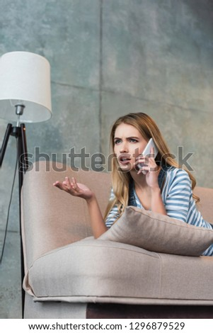 worried woman talking on smartphone and lying on pink sofa #1296879529
