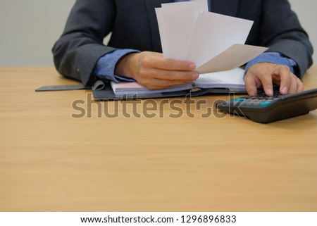 man calculate domestic bills. Businessman using calculator checking balance & costs. Startup counting finance for paying taxes at office #1296896833