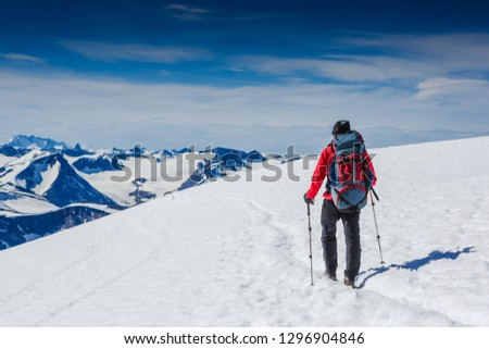 Hiker with backpack walking on snowy trail in Norway #1296904846