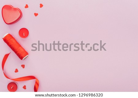 top view of paper hearts, thread and candles isolated on pink with copy space, st valentines day concept #1296986320