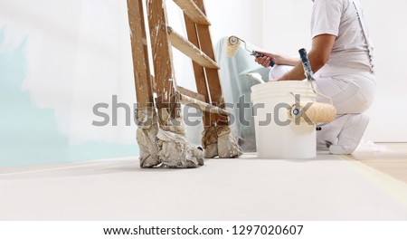 painter man at work with a roller, bucket and scale, from below view, copy space template #1297020607