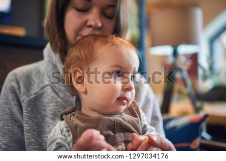mother with an 1 year old baby sitting on a sofa at home. #1297034176