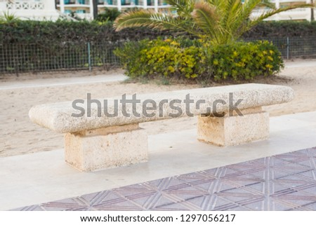 Stone bench in the city park outdoors #1297056217