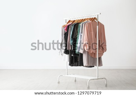 Wardrobe rack with stylish clothes near white wall indoors. Space for text Royalty-Free Stock Photo #1297079719