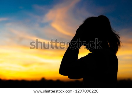 Silhouette woman standing sad in the sunset. #1297098220