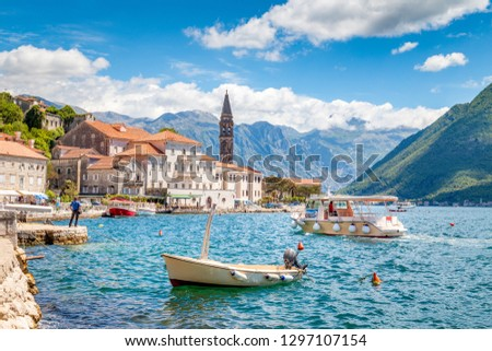 Scenic panorama view of the historic town of Perast at famous Bay of Kotor with boats on a beautiful sunny day with blue sky and clouds in summer, Montenegro, southern Europe #1297107154